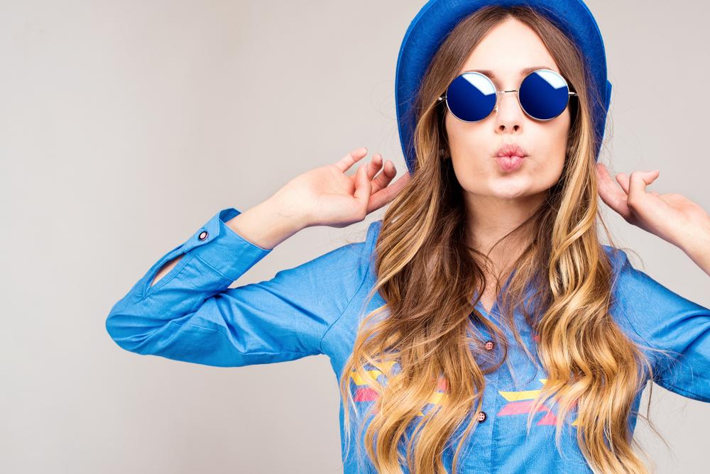 Junges Model posiert mit Hut und Sonnenbrille vor Kamera